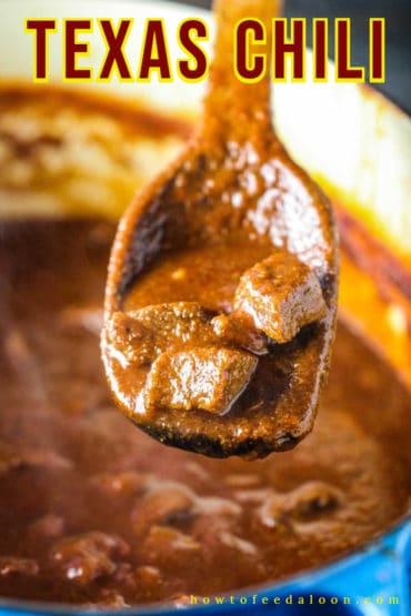 A wooden spoon holding up a spoonful of authentic Texas chili.