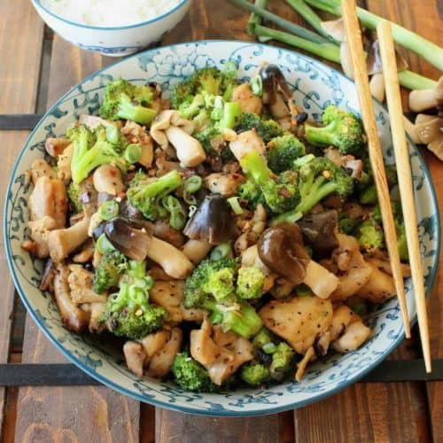 chicken and mushroom stir fry in a bowl with chop sticks on the side