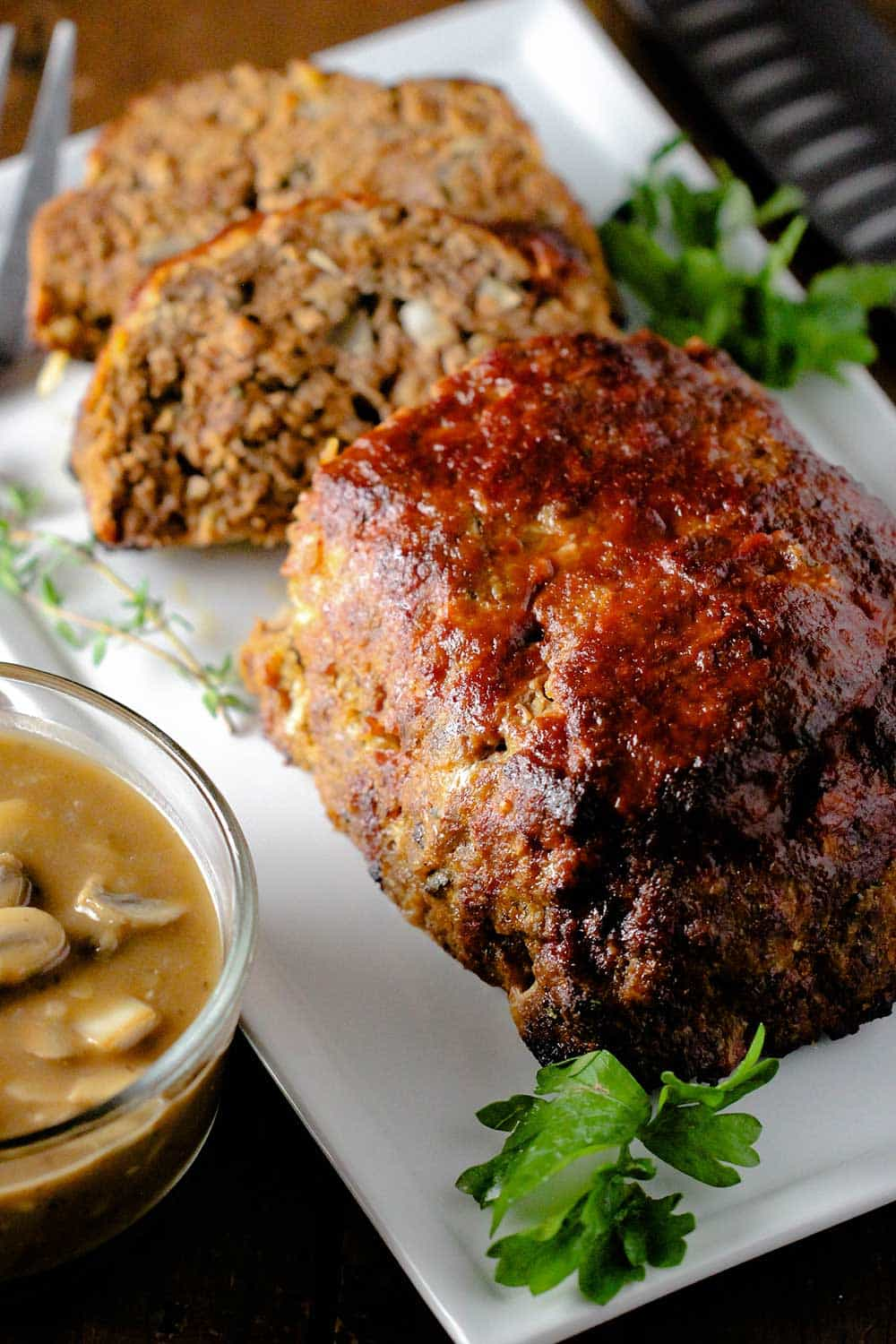 A best-ever meatloaf on a white platter next to a bowl of mushroom gravy.