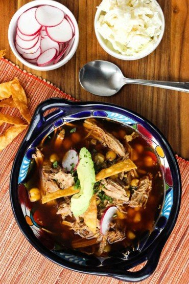 Pozole Rojas in a bowl with another bowl of radishes and cheese
