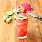 A tall glass holding a Mexican Sea Breeze Cocktail with a pink straw on a wood cutting board with lime slices