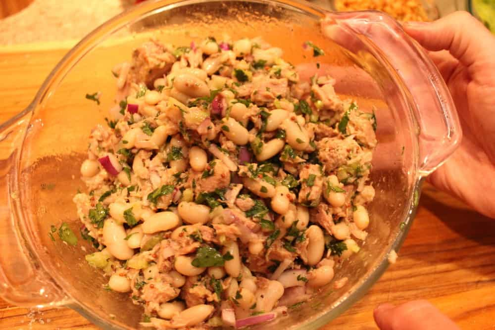 A hand holding a glass dish with tuna salad mixture