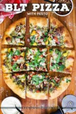 A overhead view of a BLT pizza cut into squares on a wooden cutting board with a small bowl of red pepper flakes and a bowl of Parmesan cheese nearby.