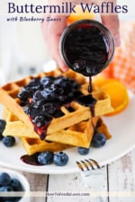 A hand pouring a blueberry sauce over a stack of buttermilk waffles on a white plate next to a fork.