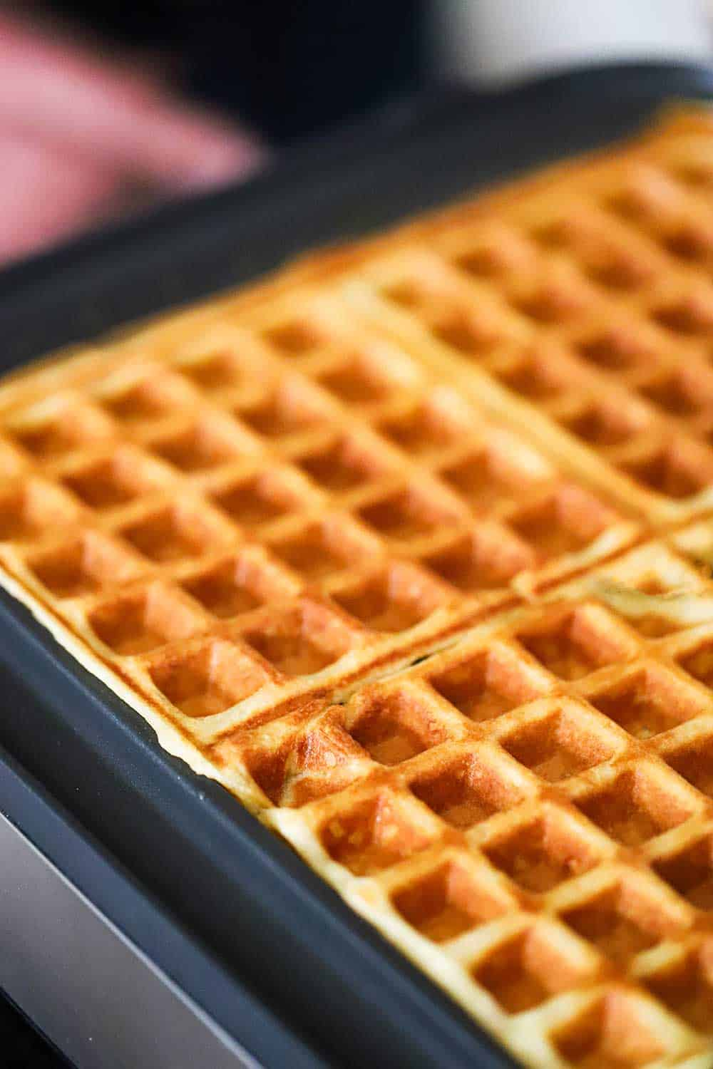 Fully cooked waffles in a square waffle maker with the lid up exposing the waffles.