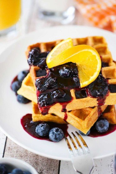 A stack of buttermilk waffles topped with a blueberry sauce and a slice or orange all on a white plate with a fork next to it.