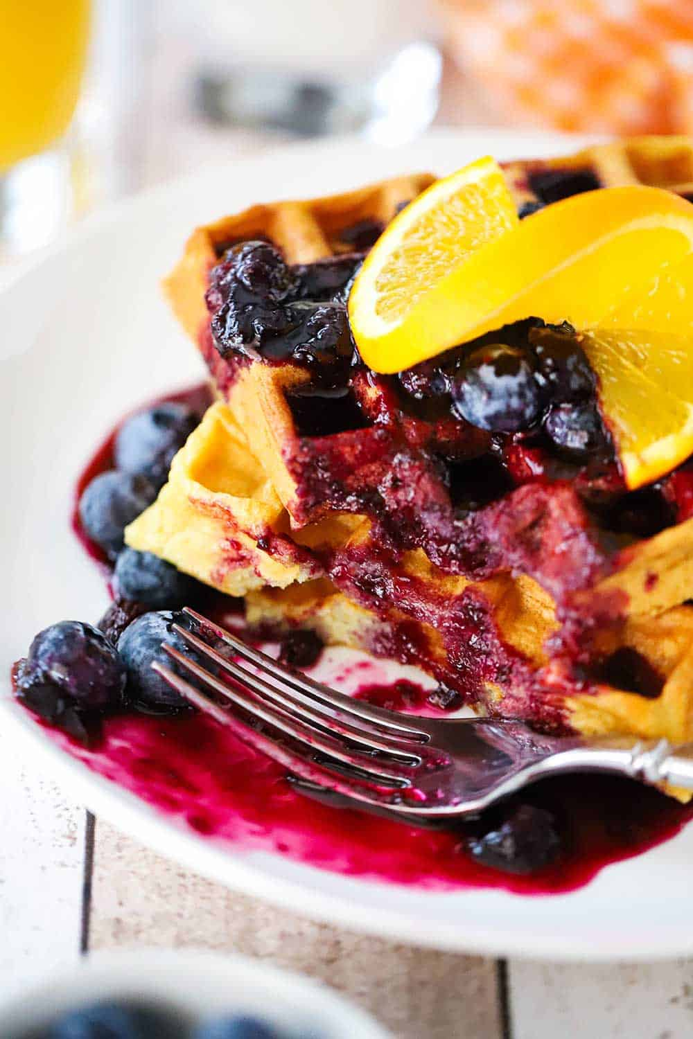 A white plate filled with a stack of buttermilk waffles and blueberry sauce with a bite take out of it.