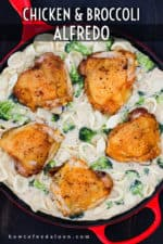An overhead view of a large red skillet holding seared chicken thighs in a broccoli and pasta alfredo sauce.