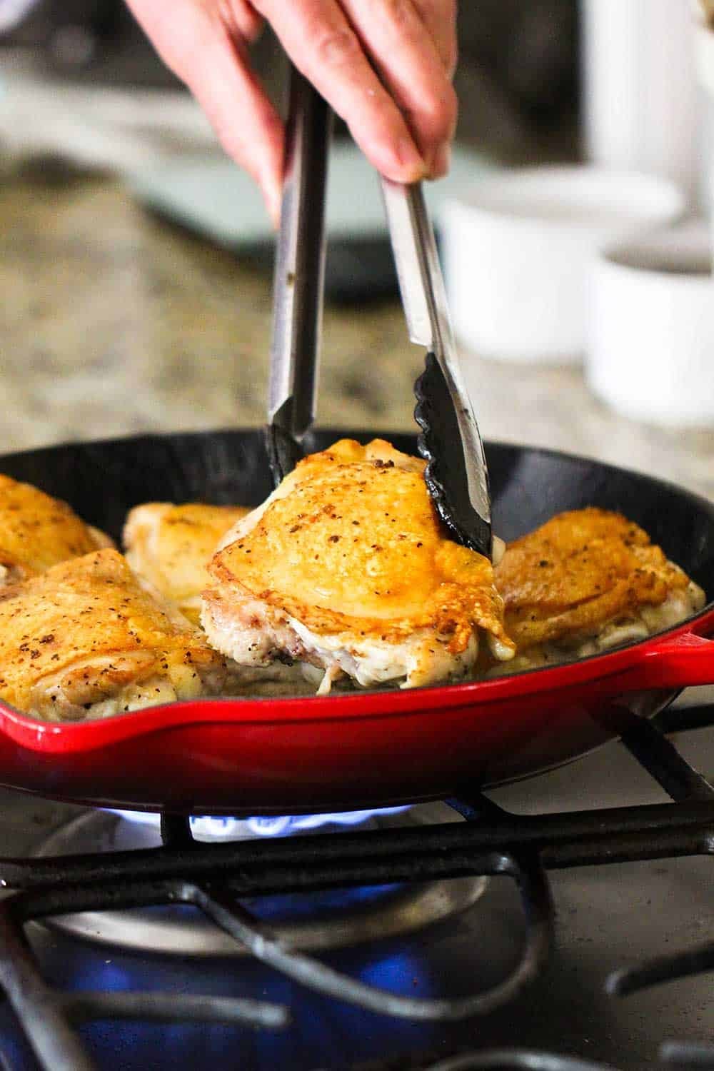 A hand using a pair of tongs to sear chicken thighs in a large red skillet on the stove.