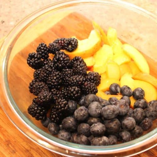 Fresh peaches, blueberries and blackberries in a glass bowl sitting on top of a wood cutting board