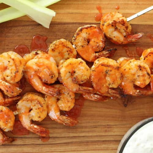 Skewers of grilled buffalo shrimp on a wooden cutting board