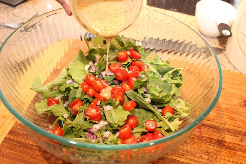 An arugula salad with tomatoes, red onion and mustard vinaigrette is perfect