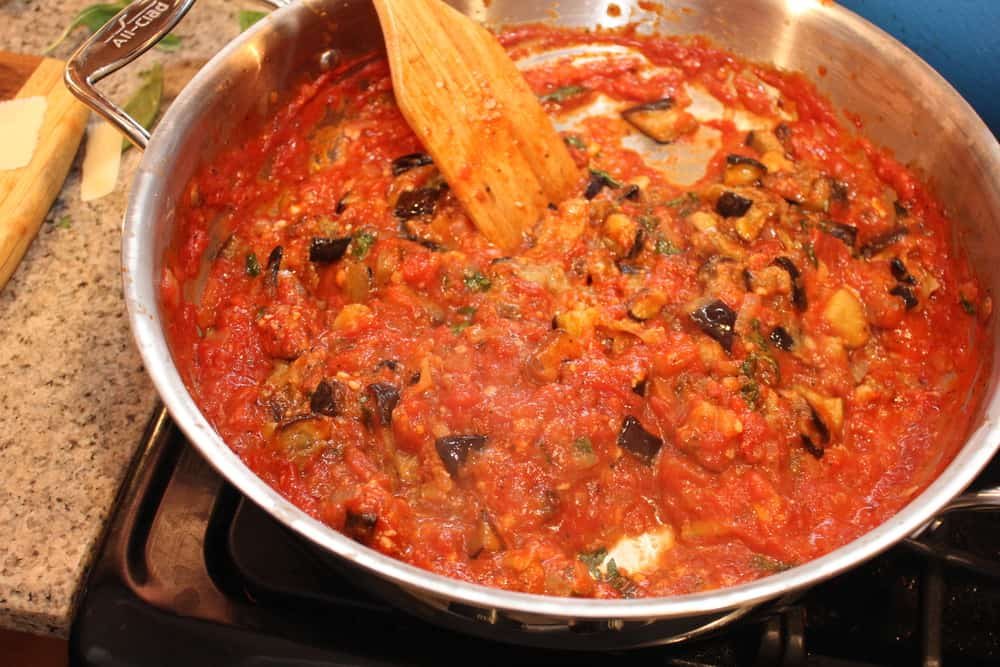A large silver skillet filled with the sauce for Pasta alla Norma