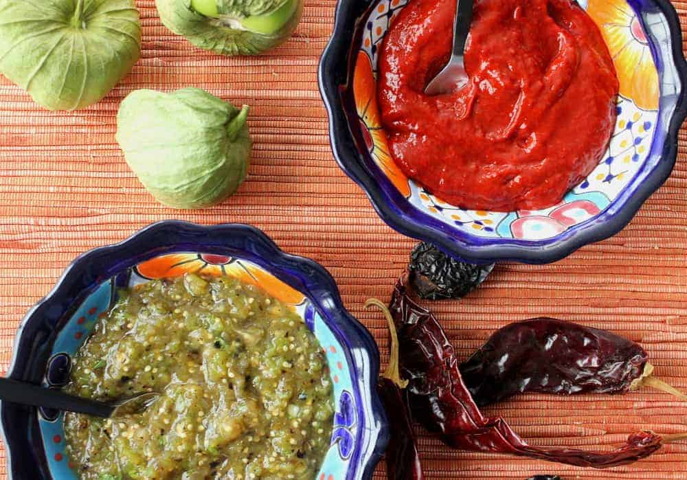 A bowl of roja salsa next to a bowl of roasted verde salsa