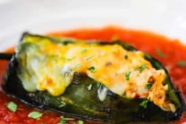 A stuffed poblano pepper on a white plate filled with a red sauce.