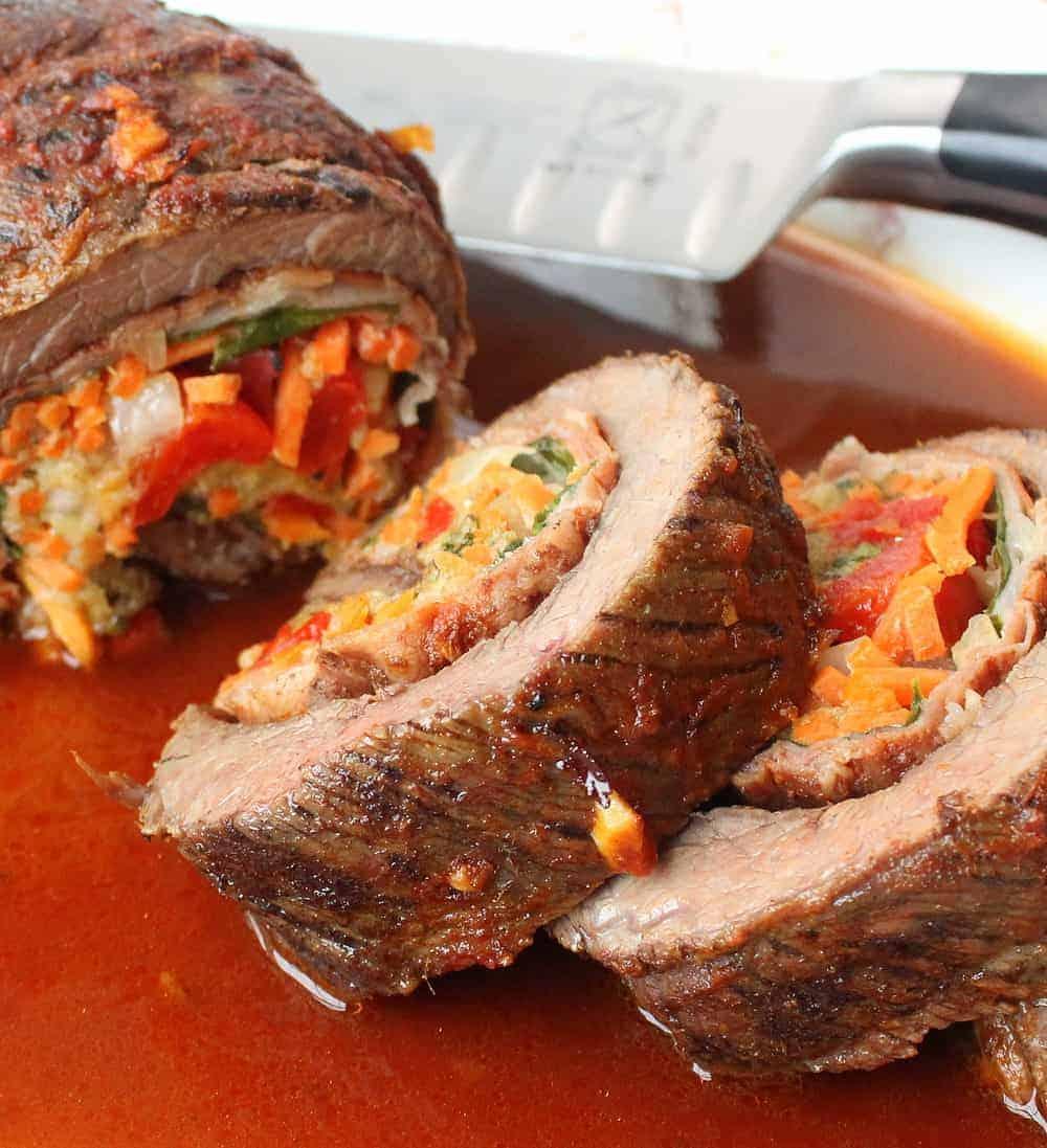 A sliced stuffed flank steak on a platter in a sauce.