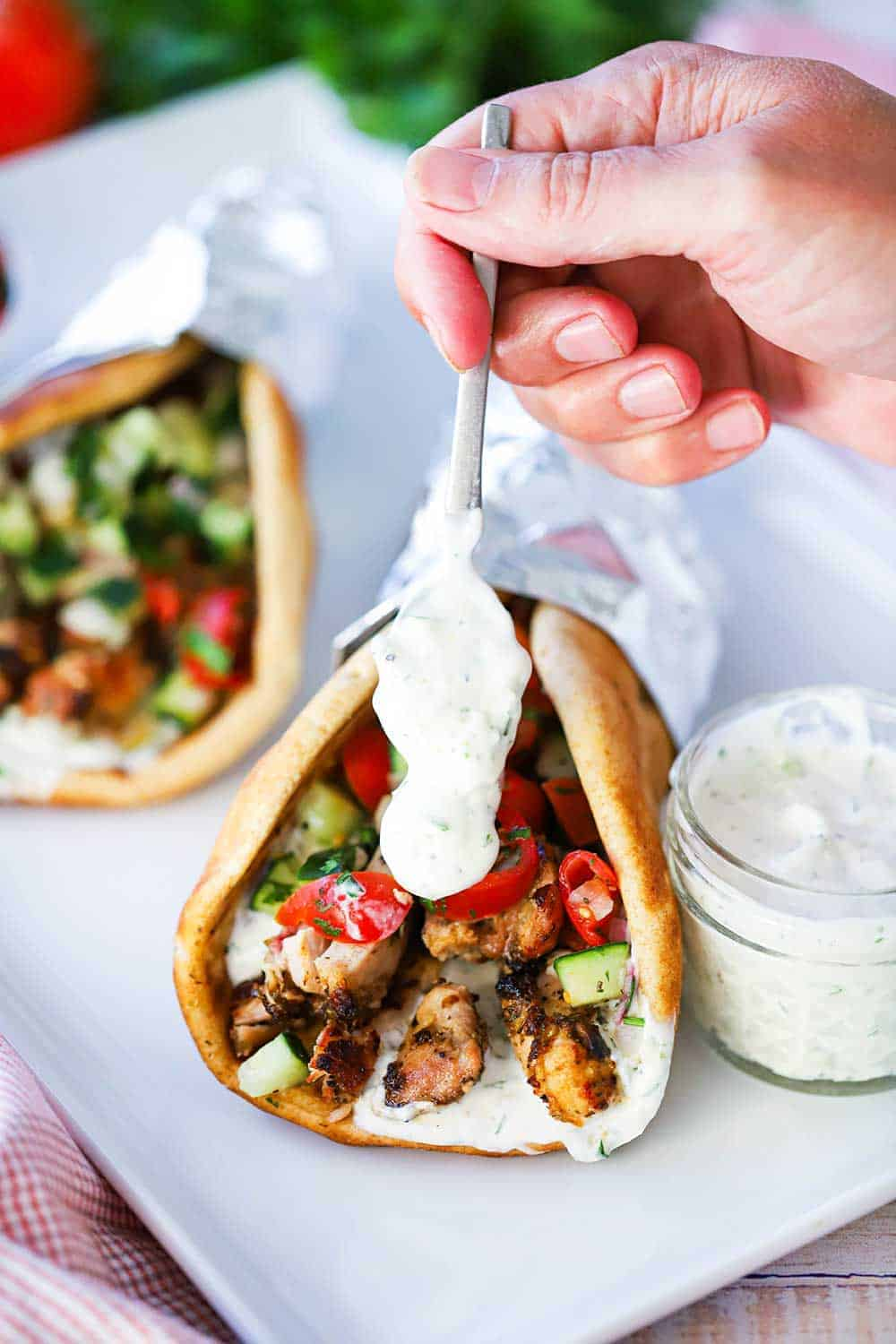 A hand using a small spoon to drizzle homemade tzatziki sauce over the end of a chicken gyro that is sitting next to a small jar of the sauce on a white platter.