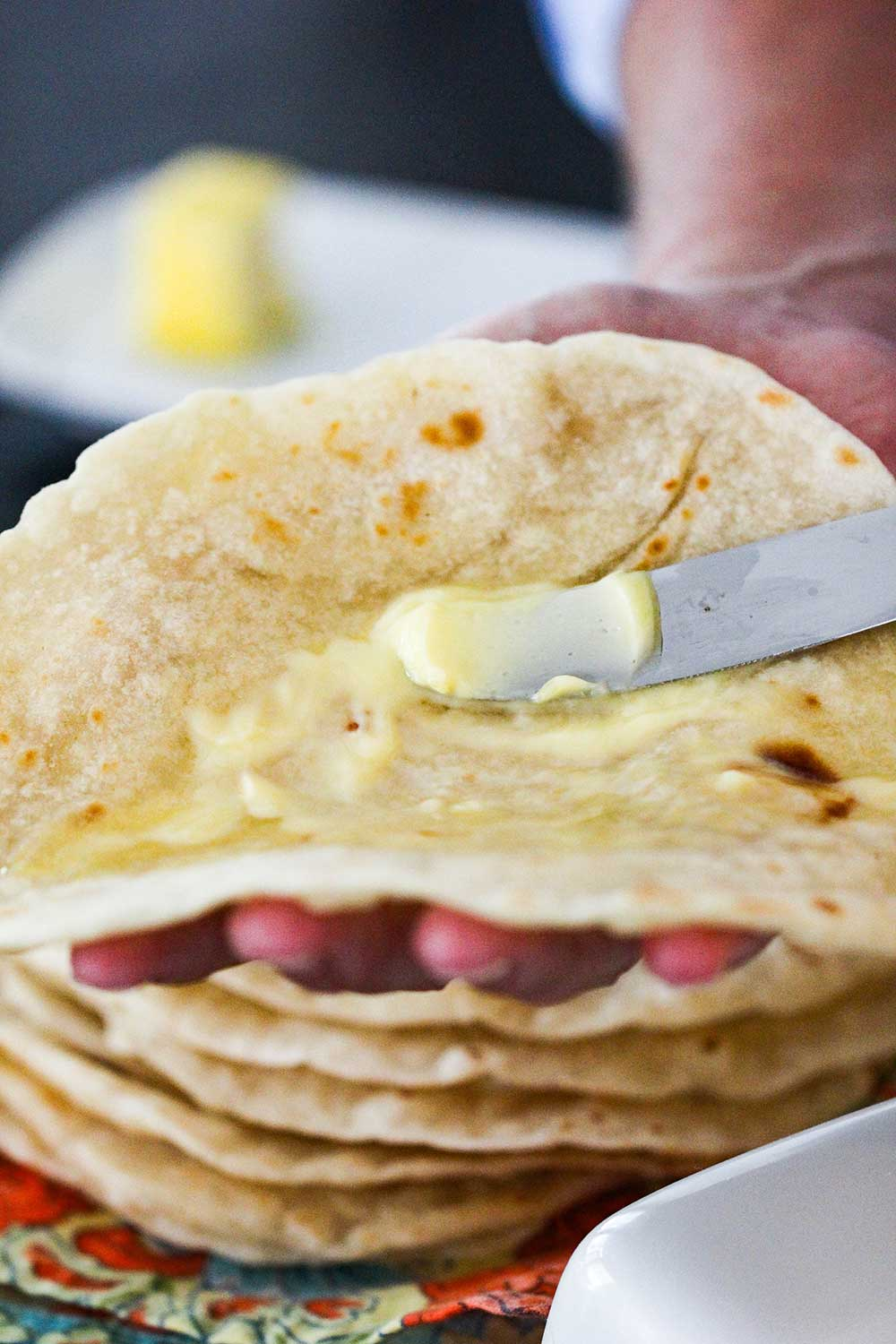 A knife spreading butter onto a warm homemade flour tortilla.