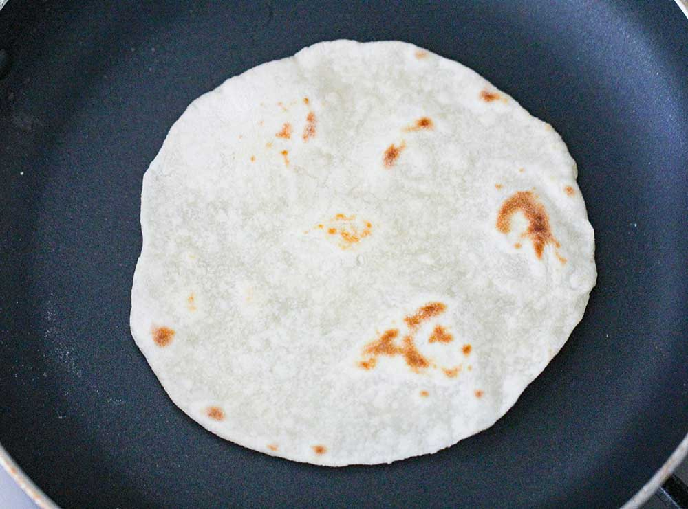A flour tortilla cooking in a black skillet.