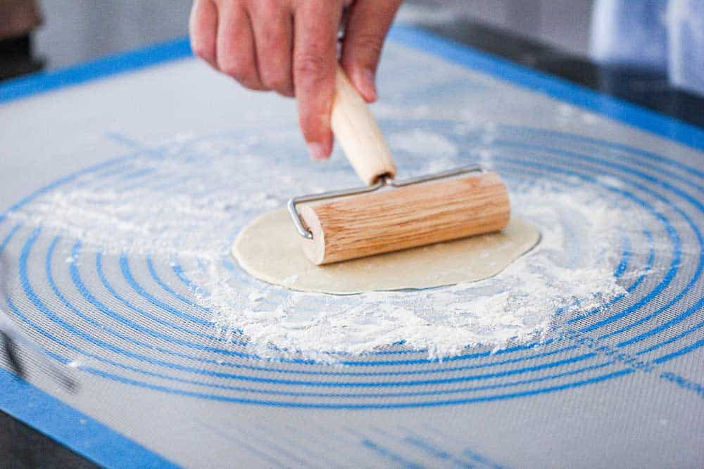 A pastry roller stretching out dough for homemade flour tortillas.