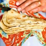 Hands holding a stack of homemade flour tortillas in a colorful cloth.