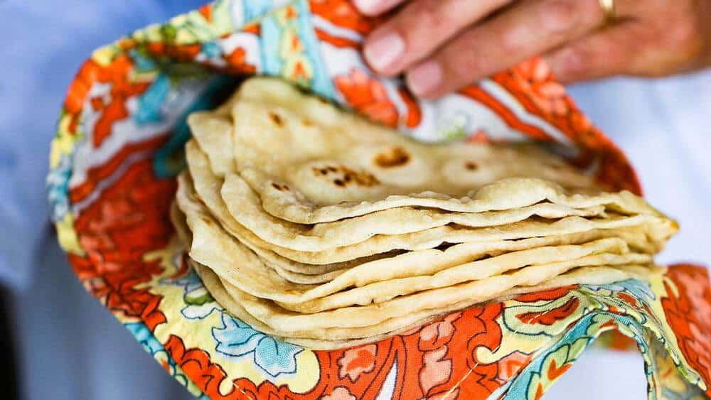 A hand holding a stack of homemade flour tortillas in a colorful cloth.
