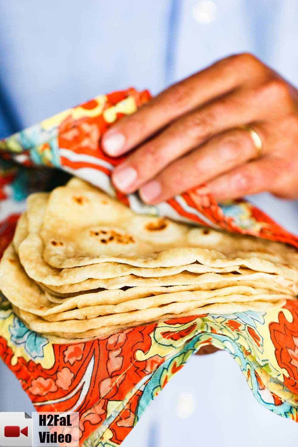A stack of homemade flour tortillas being held by two hands in a Mexican cloth.