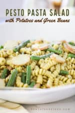 A close up view of a large circular white serving bowl filled with pesto pasta salad with sliced potatoes and green beans.