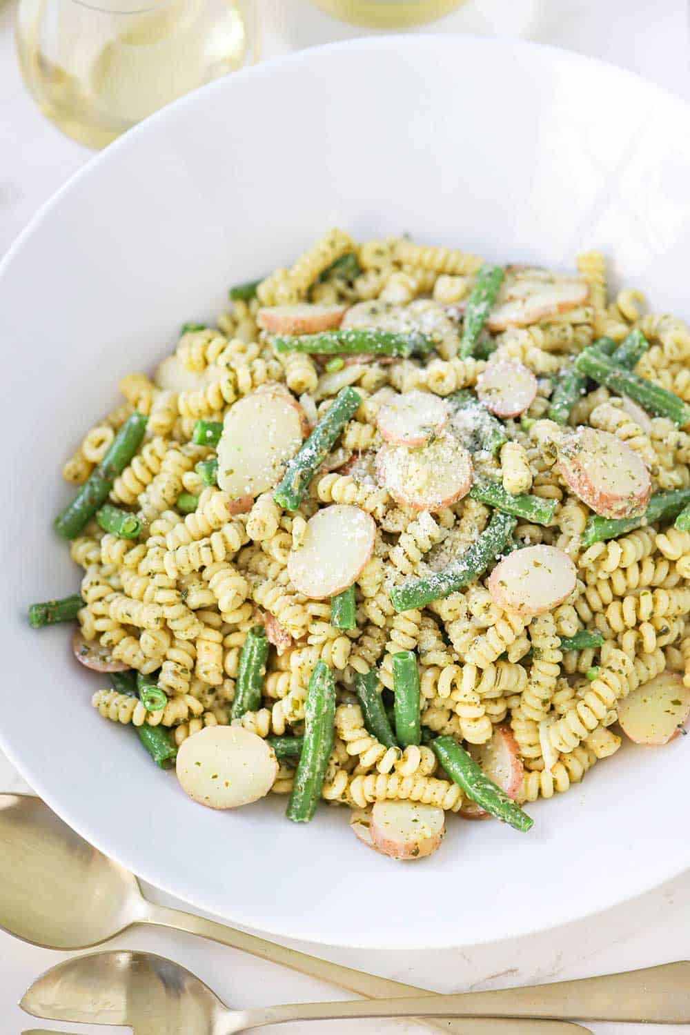 A white bowl of pesto pasta with potatoes and green beans.