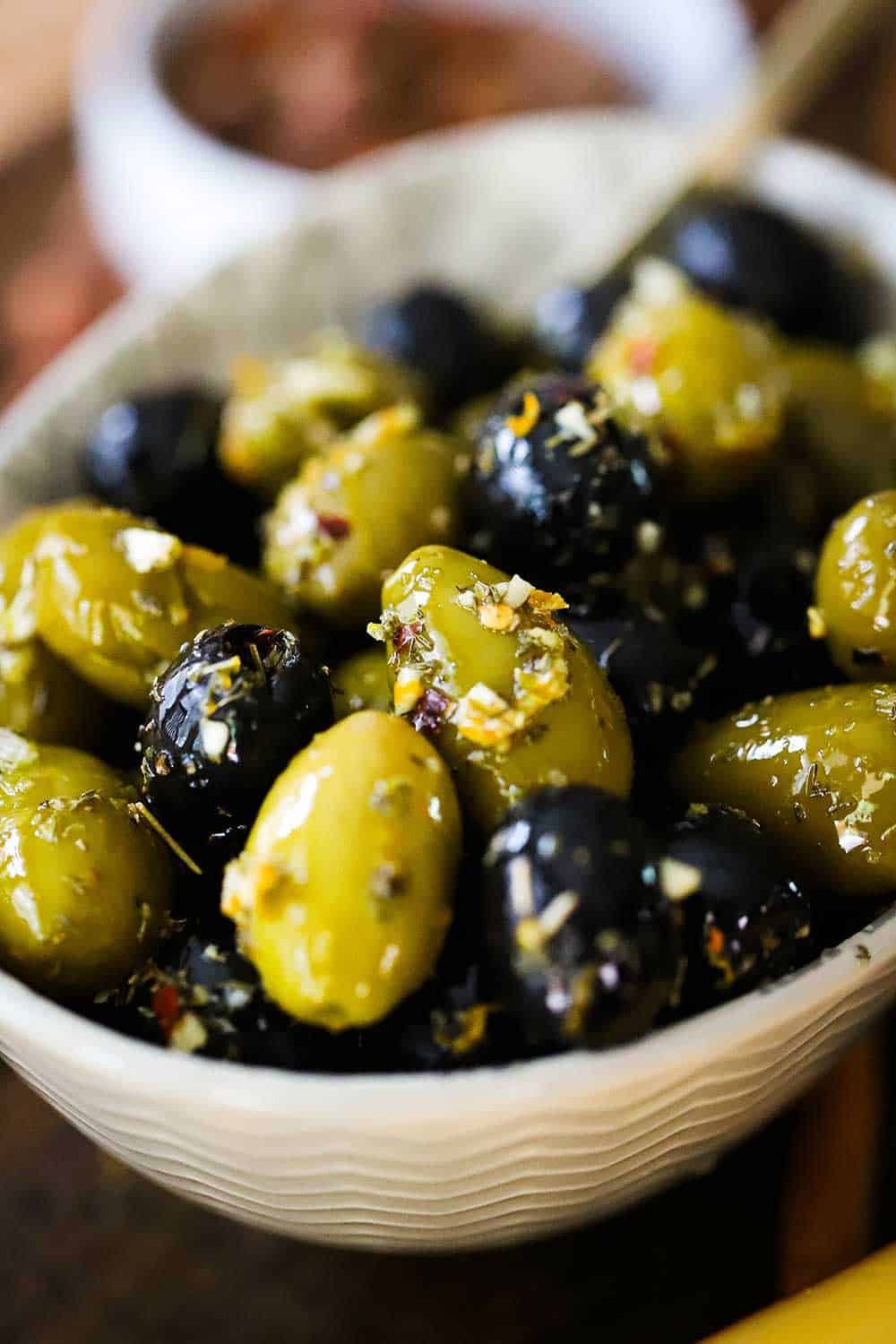 A small white oval bowl filled with green and black marinated olives.