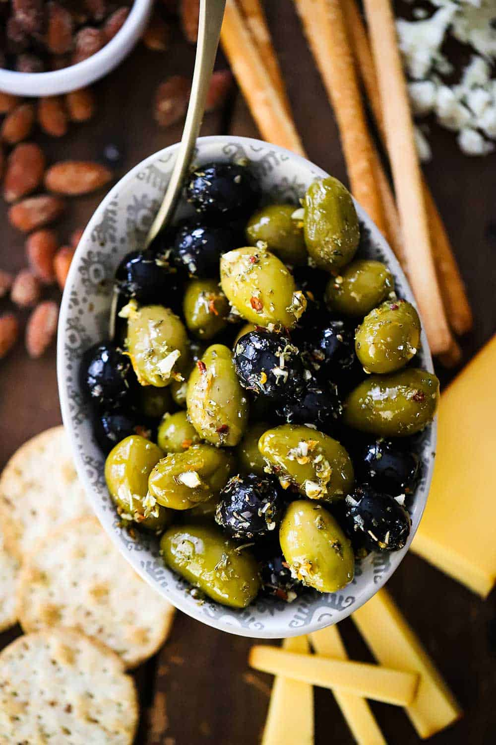 A small oval bowl filled with marinated olives surrounded by cheese slices, crackers, bread sticks, and almonds.