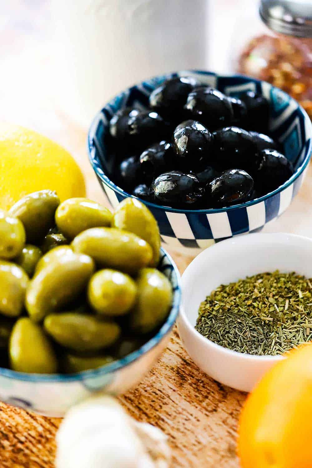 One small bowl holding green olives and another bowl holding black olives surround by dried herbs, an orange, and an olive oil dispenser.