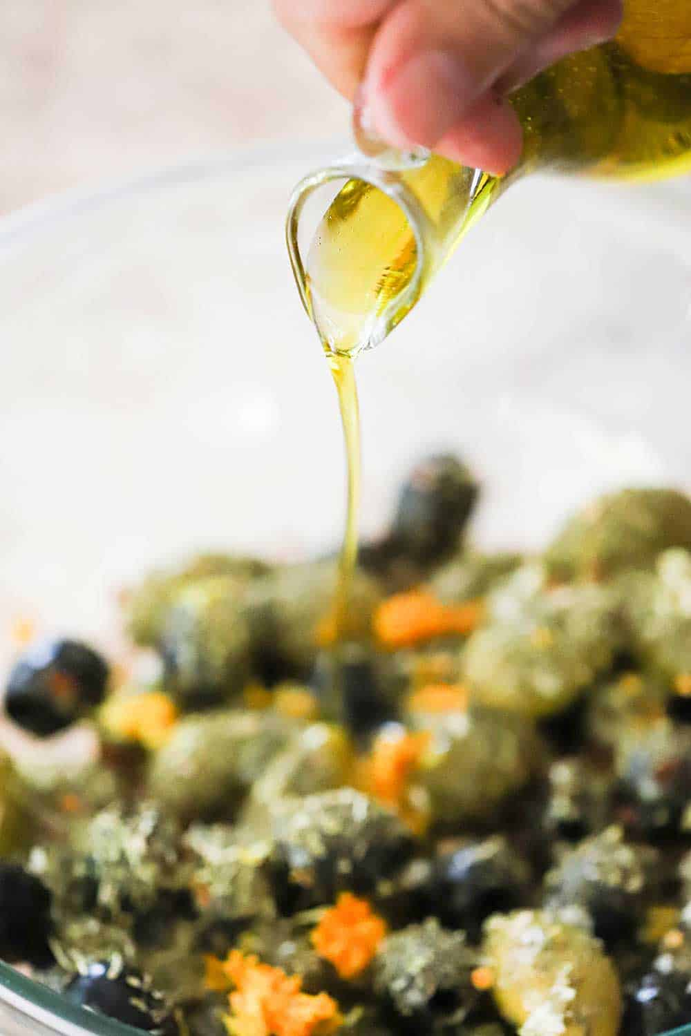 A hand pouring olive oil from a glass oil holder into a glass bowl filled with marinated olives.