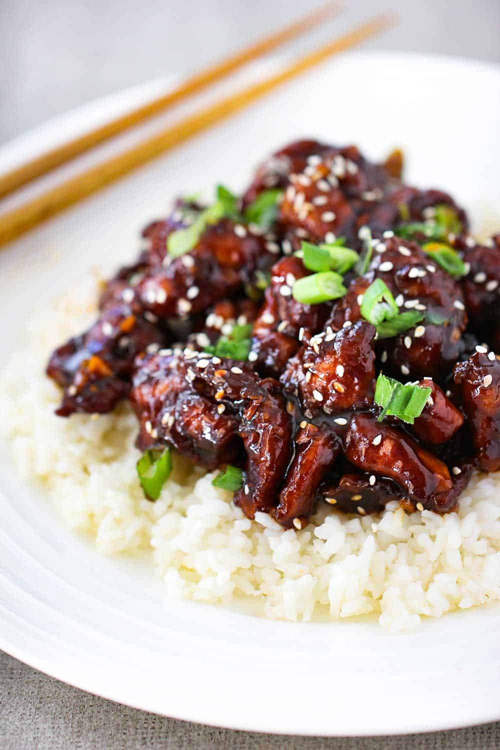 A white plate of General Tso's Chicken on a bed of white rice with a pair of chop sticks nearby.