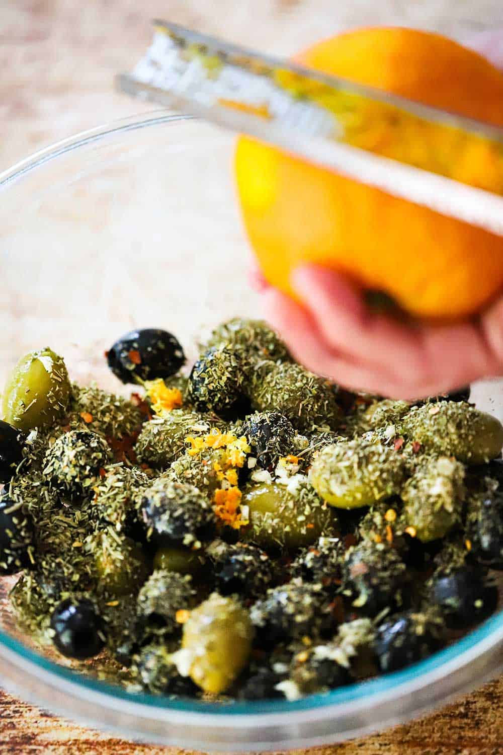 A person using a citrus zester to collect zest from an orange over a bowl of black and green olives topped with dried herbs.