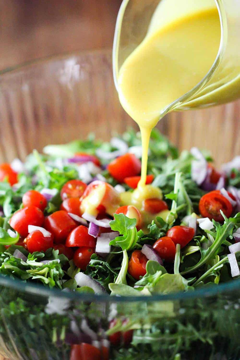 Arugula salad with tomatoes in a glass bowl with vinaigrette being poured over it.
