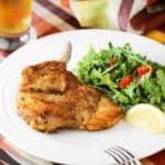 Pork Milanese on a white plate next to an arugula salad and lemon wedge.