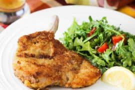 Pork Milanese with arugula salad on a white plate with glass of beer nearby.