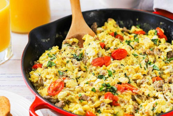 A large red skillet filled with an Italian skillet scramble next to a white bowl filled with fresh fruit.