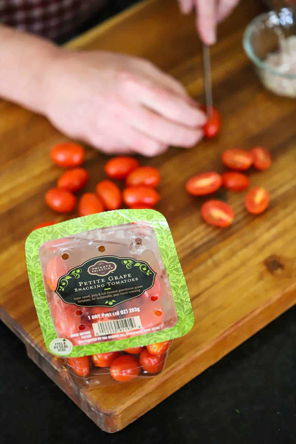 A person using a small knife to slice grape tomatoes in half on a cutting board in front of a package of the tomatoes.