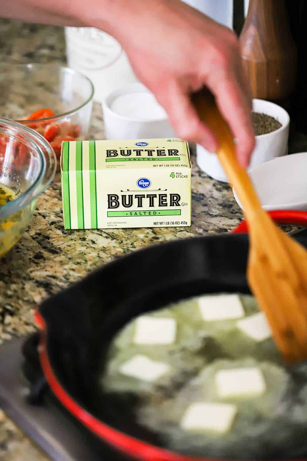 A person using a wooden spatula to help butter melt in a heated skillet all sitting in front of a box of Kroger salted butter.