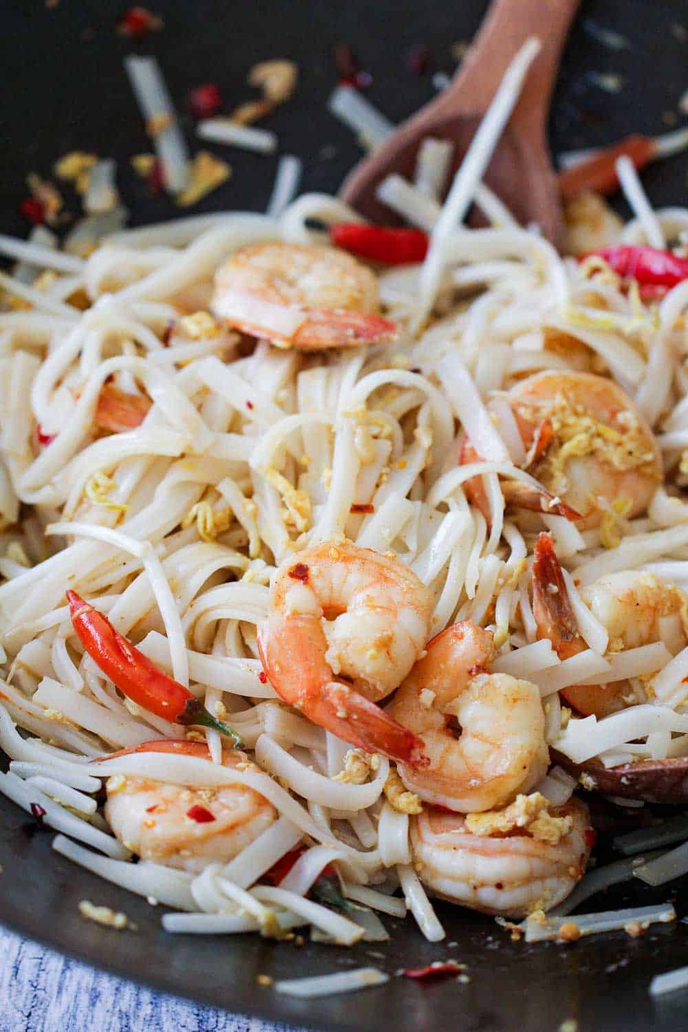 A close up view of authentic shrimp pad Thai in a wok.