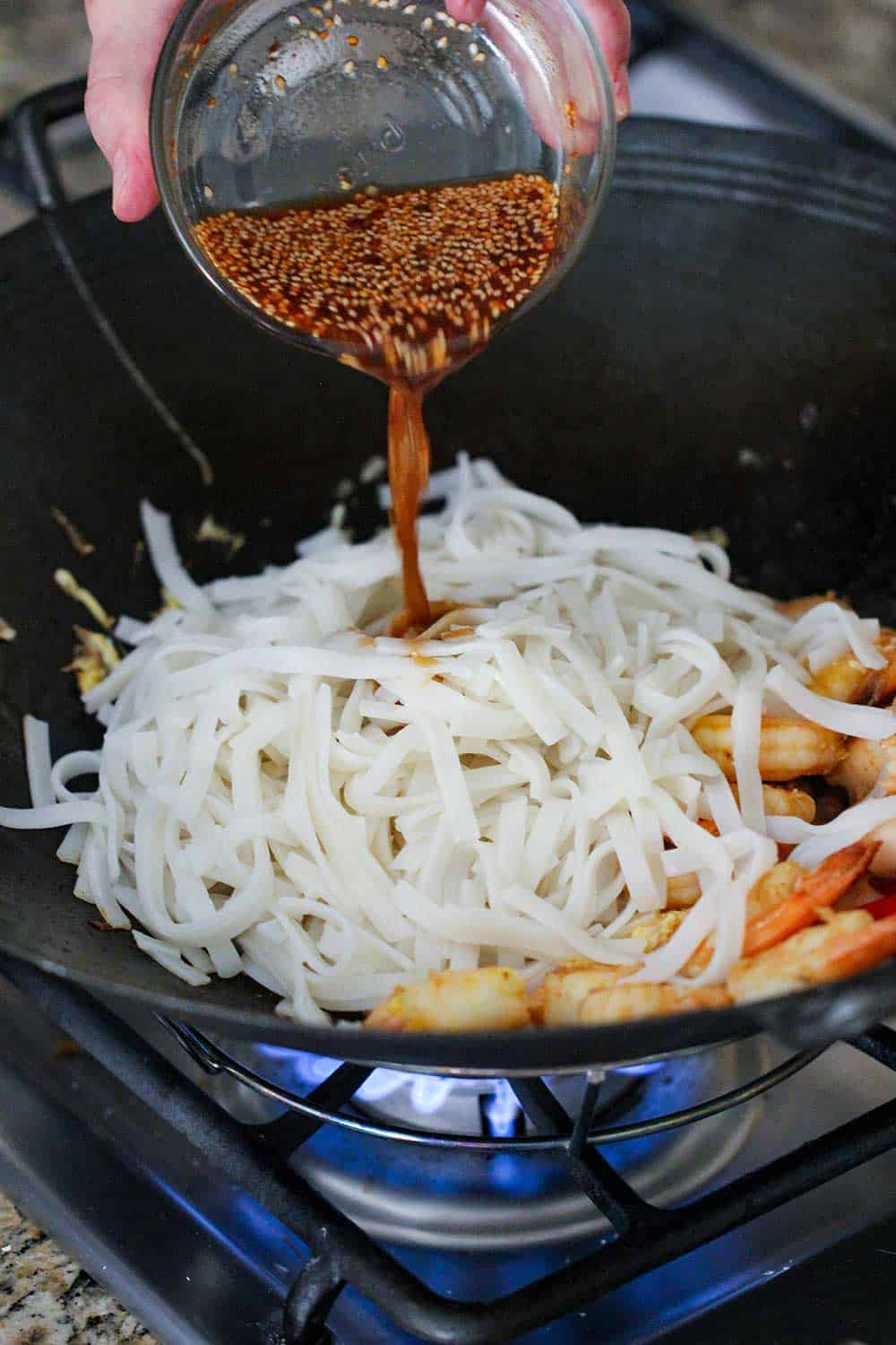 A hand pouring pad Thai sauce into a wok filled with rice noodles.