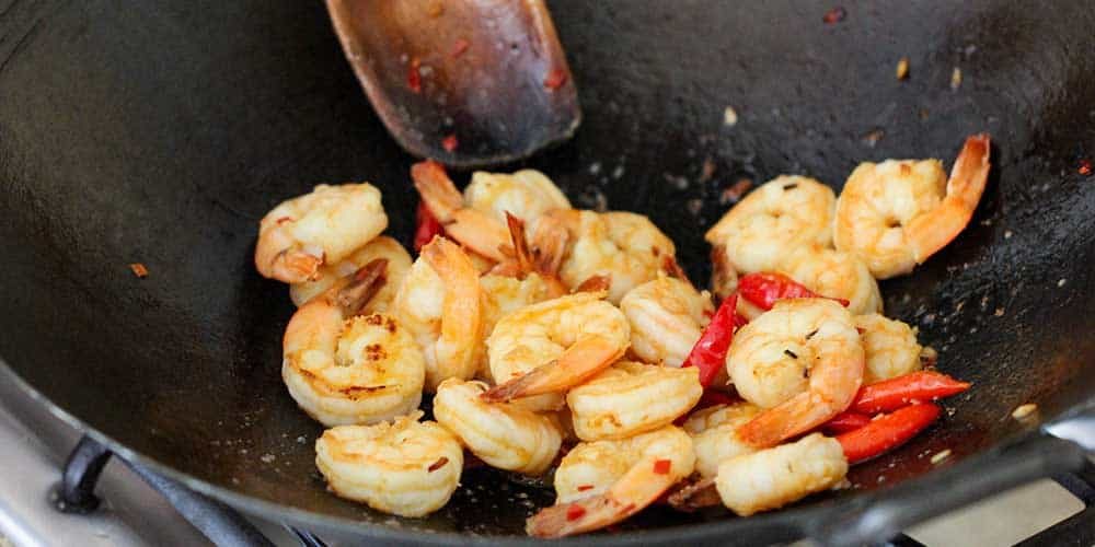Shrimp being stir-fried in a wok for authentic shrimp pad Thai.