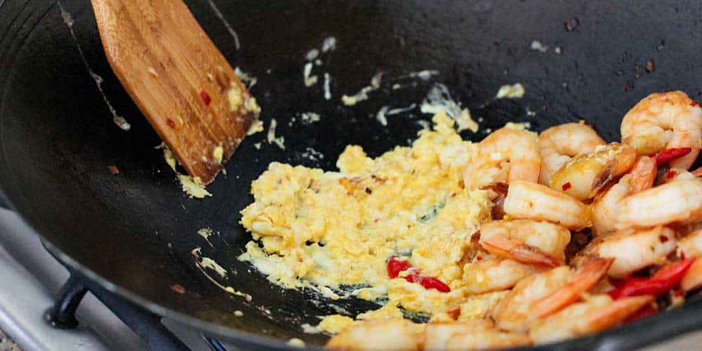 Two eggs being scramble with shrimp and red peppers in a large wok with a wooden spoon.