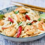 A close up view of authentic shrimp pad Thai in a colorful bowl with chop sticks next to it.