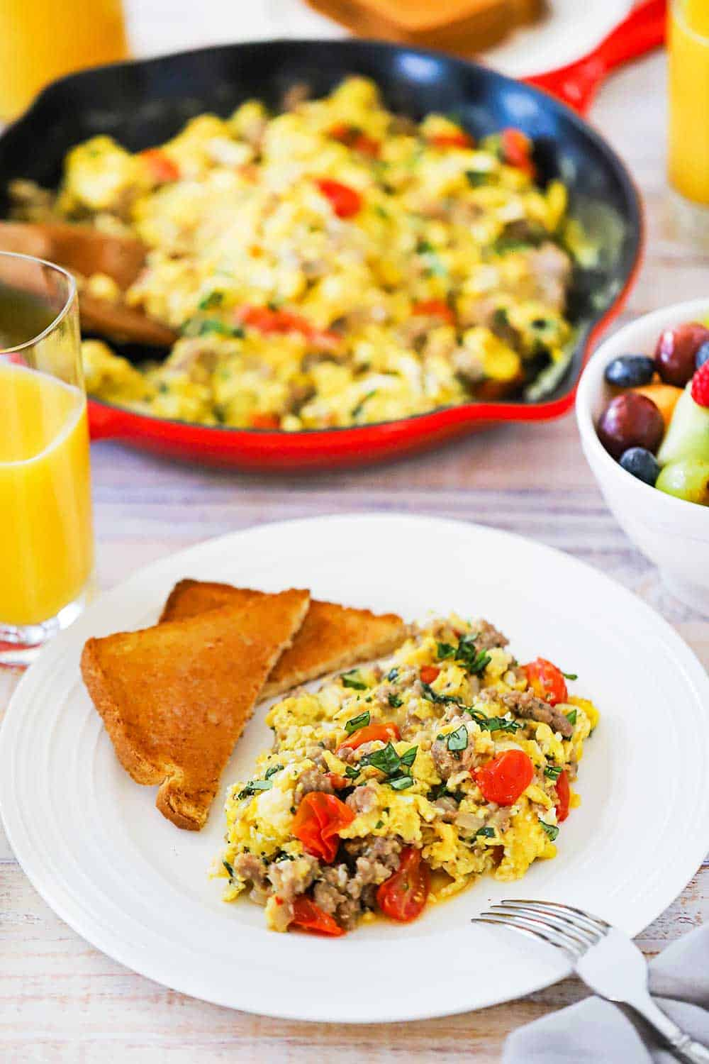 A white dinner plate filled with a large helping of Italian skillet scramble next to a couple pieces of toast cut in half, all next to a large skillet filled with the scrambled dish.