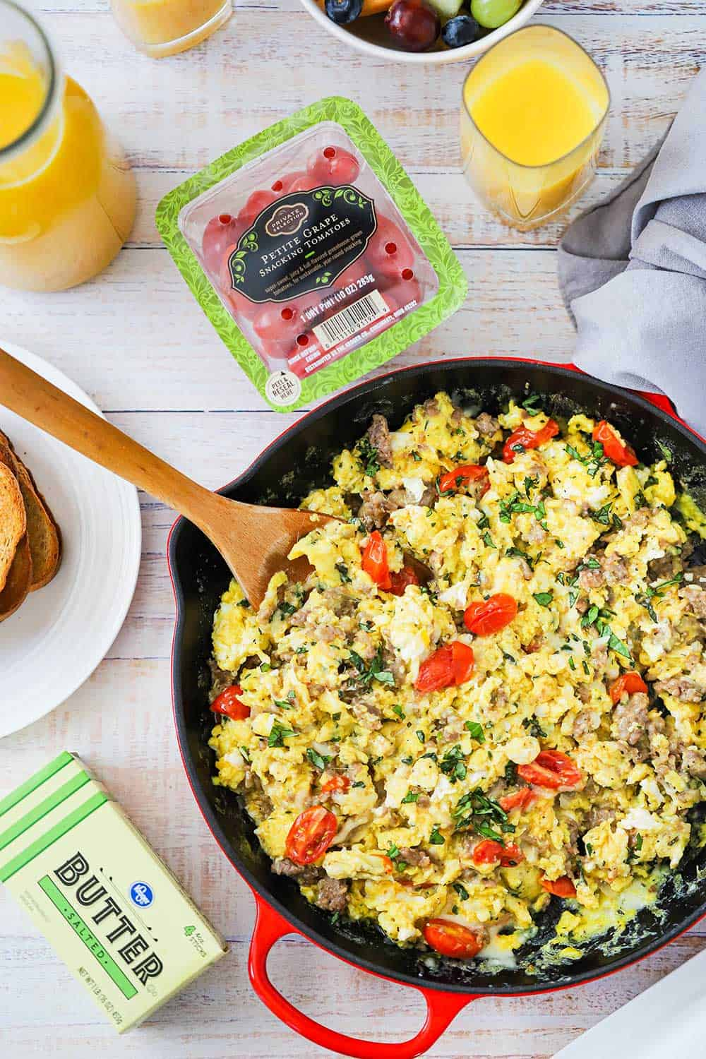 A large red skillet filled with Italian skillet scramble and flanked by Kroger butter, grape tomatoes, and two glasses of orange juice.