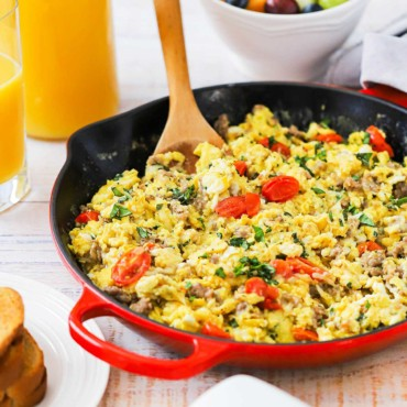 A large red skillet filed with Italian Skillet Scramble with a wooden spoon inserted into it all next to a couple of glasses of orange juice.
