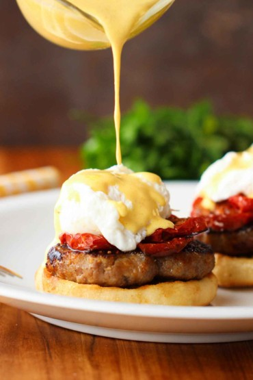 A white plate with Eggs Blackstone with Sausage being drizzled with hollandaise sauce